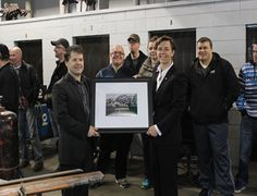 Academy Canada Director, James Loder, presents a piece of Newfoundland artwork to Dr. Kelli Leitch.