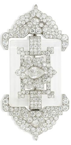 AN ART DECO ROCK CRYSTAL AND DIAMOND BROOCH, BY CARTIER, CIRCA 1920. Of Indo-Persian influence, the central old-cut pear shaped diamond to a pavé-set diamond stylised lotus flower surround, within a polished rectangular rock crystal frame, flanked to either side by diamond pieced geometric arrowhead terminals, 8.5cm, with French assay marks for platinum, signed Cartier, numbered. #Cartier #ArtDeco #brooch