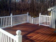 Deck with white rails and a stained floor