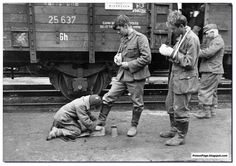 Trying to make a living in difficult times. A Russian boys cleans the boots of German soldiers at a Russian railway station. 1943.