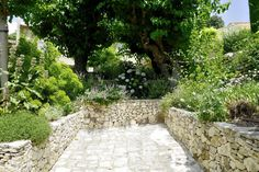 Rustic Stone Wall retaining a hillside planted with hydrangea + Perennials Saint-Victor-des-Oules | SCAPE DESIGN