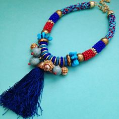You'll fall in love with this intricate hand beaded necklace. Tassel Me This is a stunning show stopper bib necklace with hundreds of blue and red beads and a gorgeous tassel.