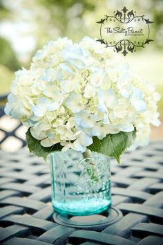 Love the white hydrangeas in this with the tint of blue with the blue mason jar!