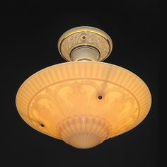 A wonderful 1930s Art Deco floral design in relief on the outer surface of the vintage custard glass. The shade is suspended below the light bulb with 3 chains or metal hangers capturing the shade with a small ball recessed into the shade. The cream porcelain ceiling fixture has hand painted gold stripes and is a recognized fixture as Porcelier.  http://www.vintagelights.com/product/1/embossed-custard-glass-ceiling-fixture-vintage-art-deco.html