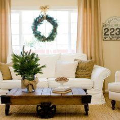 Adding a few pieces of greenery to your living room makes the whole space feel earthy and rustic. More living room decor ideas: http://www.bhg.com/christmas/indoor-decorating/pretty-christmas-living-rooms/?socsrc=bhgpin121113accentacentraltable&page=16