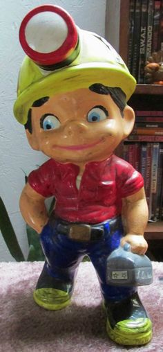 """I painted this ceramic """"little miner"""" in my husband's """"image"""".right down to his favorite red shirt with the rolled up sleeves, blue jeans and his """"bumblebee"""" (black and yellow) mining boots and red and black caplamp."""