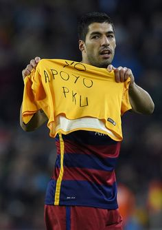 """Barcelona's Uruguayan forward Luis Suarez displays a jersey reading """"I support PKU"""" as he celebrates after scoring during the Spanish league football match FC Barcelona vs Real Sporting de Gijon at the Camp Nou stadium in Barcelona on April 23, 2016."""