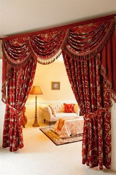This decadent rich red curtain set will transform your living room into the Louis XVI palace. It is nothing short of regal as it holds court no matter where you decide to feature it. gold, red, brown,curtain, curtains, draperies, drapes, elegant, floral, fringe, gold, jabots, luxury, ready made, silk, swag, swags, valance, valances, window treatment,