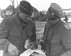 "Commander of the 1st Company, 3rd Tank Regiment SS Division ""Totenkopf"" - SS-Hauptsturmführer Erwin Mayerdress (Hubert-Erwin Meierdress) and commander of the 1st Reconnaissance Battalion Division ""Leibstandarte SS Adolf Hitler"" Obersturmbannfuehrer SS Kurt Meyer (Kurt Adolf Wilhelm Meyer ) over the map fighting. Part of the 1st SS Division and the 3rd SS Division, advancing on Kharkov, met in the village near Kharkov Peresechnaya March 9, 1943."