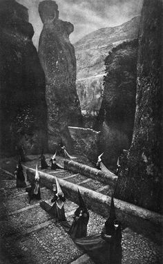 """WORSHIPPERS OF CTHULHU ON R'LYEH. An extremely rare photograph by an unknown artist in 1934 depicts the """"Cyclopean ruins"""" of R'lyeh, the fabled island in the Pacific somewhere near Easter Island. Here, hatted, chanting cultists carrying ceremonial objects process up steps clearly designed for beings larger than human. R'lyeh occasionally rises when certain astronomical phenomena are correct. In the background stands a semi-anthropoidal statue with face and brow in profile, looking…"""