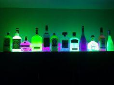 glow in the dark liquor bottles above cabinet.  #basement #bar