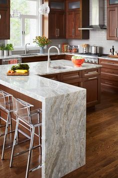 12 Great Kitchen Island Ideas | Traditional Home. L-shape island with dramatic waterfall edges—serving as a high-function focal point. The stylish surface—Fantasy Brown Quartzite—lends extra drama to the scene with color and texture variations that could almost double as art.