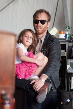 The Black Keys' Dan Auerbach has his daughter Sadie sit on his lap at the 2013 New Orleans Jazz & Heritage Music Festival.