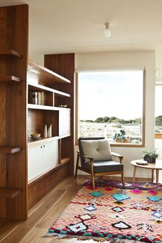Neutral furniture in living room with built-in bookshelf and view of city