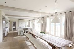 british barn conversions | open kitchen with extra long dining room table, bench seating, french ...