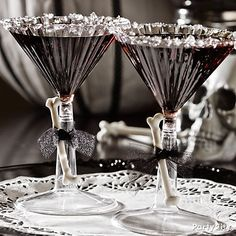 Black Martinis for Halloween. Mix 3 1/2 oz. black vodka with 1/2 oz. black raspberry liqueur in a cocktail shaker with ice. Rim the glasses with bits white rock candy. There ya go.