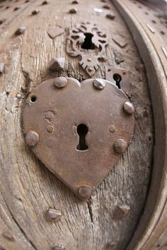 A very old wooden door with an interesting series of different metal keyholes.