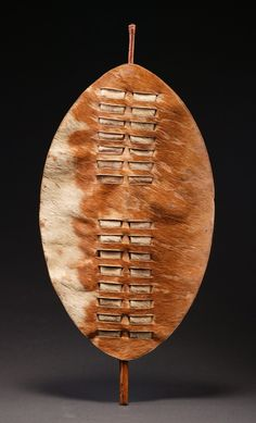 Small Zulu shield made for ceremonial dance or young warriors. Cow hide with the brown and white hair being in good condition. The back is cut and folded with the original stick handle still intact. The overall patina is good from age and use. Mid to late 19th century, South Africa.