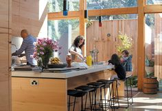 In this Australian renovation, the large, naturally lit kitchen is the heart of the house. Messmate-clad cupboards and huge expanses of glass dominate the space where Angelucci uses the sink, Gorman works at the kitchen island, and Pepa and Hazel look on. Play in the courtyard between the kitchen and garage is easily supervised and enclosed from the alley behind the house. Photo by: Stephen Oxenbury
