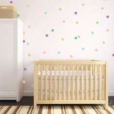 Small confetti polka dot wall decals in a nursery in a variety of pastel colors spaced out evenly in a pattern on a white wall. The room has a wooden crib and a white dresser.