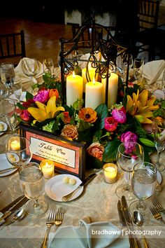 centerpiece with quote on table number -i love the candles in the open cage with flowers around LOVE THIS!!!