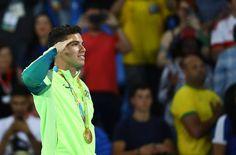O brasileiro Thiago Braz presta continência no pódio, após conquistar a medalha…