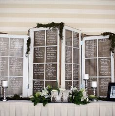 Using old furniture pieces (like shuttered windows, antique dressers, and coffee tables) is hugely popular as wedding reception decor -- and we love the way this display of white glass window shutters, trimmed with a little greenery, pulls off the trend.