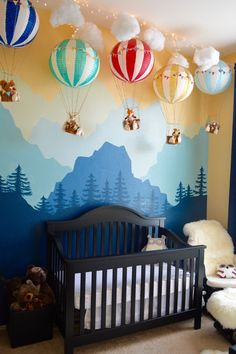 So fun decor for baby room with mountain wall mural and hot air balloon toys