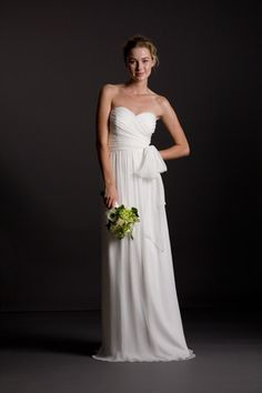 Strapless sweetheart dress with side ruching. Decorative covered buttons along left side seam zipper. Long slim A-line skirt falls from natural waist. Unattached sash included. Silk Crinkle Chiffon.