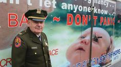 Tim Jaccard stands in front of a trailer in Wantagh, N.Y., that advertises a hotline where mothers can call to arrange to safely relinquish babies they are unwilling or unable to care for, to a responsible party.