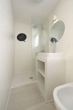 reforma baño pequeño con lavabo sobre mueble de obra, zona de ducha con mampara de vidrio, suelo de parquet.