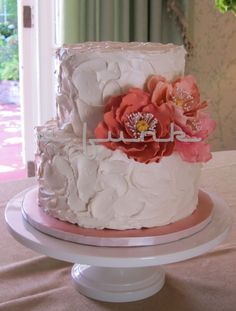 Vanilla Bean cake filled with Lemon Curd and fresh Raspberries, covered in Vanilla Swiss Meringue Buttercream with three coral sugar flowers