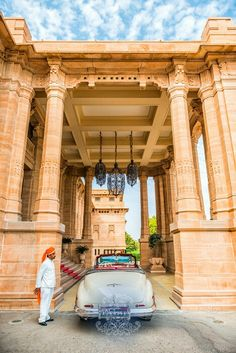 A guard and an antique car at the entrance of Umaid Bhavan Palace Hotel Jodhpur, Rajasthan, India.