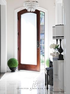 Crisp, clean entryway with beautiful hardwood door and frosted glass. Pretty crystal droplet chandelier and mirrored console table. Black lamps and stool. Stone flooring and pretty faux boxwood topiaries.