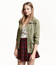 Short jacket in washed cotton twill with a high stand-up collar. Zip and wind flap at front with concealed snap fasteners, front pockets with flap and fastener, drawstring at waist, and snap fasteners at cuffs. Unlined.