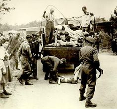 4/15/1945 - British soldiers liberate Bergen-Belsen concentration camp. They find few survivors and thousands of corpses left unburied. The soldiers force the camp guards to bury the dead prisoners.