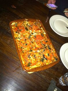 Lasagne van Jamie Oliver  Italiaans,  6 pers, bereiden 30 min, wachten 100 min  Ingrediënten  2 plakken mager rookspek 2 middelgrote uien 2 tenen knoflook 2 winterwortels 2 stengels bleekselderij olijfolie 2 tl gedroogde oregano 500 g half-om-halfgehakt 2 blikken tomatenblokjes (a 400 g) 1 bakje verse basilicum (15 g) 150 g Parmezaanse kaas 250 g lasagnevellen eier (pak a 375 g) 500 ml crème fraîche 1 grote tomaat  Voorbereiden  De bolognesesaus maken: Snijd het spek in kleine stukjes. Maak…