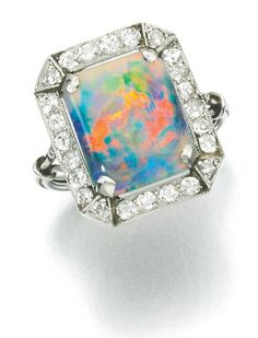 Opal and diamond ring, 1920s.  The polished opal within a frame millegrain-set with circular- and single-cut diamonds, size M. Via Sotheby's.