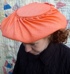 This lovely tangerine shade hat clips to your head. It has a slight wave to the middle of it. Its a striking addition to your vintage wardrobe. Bow in