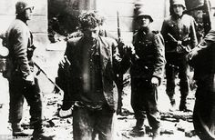 Battle of honour: A Jewish rebel is seen leaving a house surrounded by German soldiers inside the Warsaw Ghetto, during the uprising that took place in 1943.