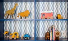 This is a detail shot of the bookcase in my twins bedroom. The walls are a solid blue, but I desperately wanted to use some wallpaper somewhere in the room, so I decided to wallpaper the interior of the shelves. The toys and books on the shelves are ever-changing, but clearly the boys love construction vehicles and animals.Pictured: Photograph by Nigel Barker