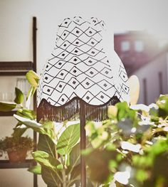 IKEA - solar powered floor lamp surrounded by plants on a balcony.