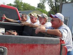 What's a farm without a pickup truck! Here, a group of farmers gather around for a morning discussion, no doubt about crops and the weather!