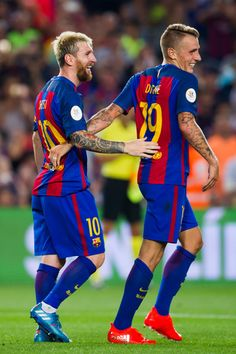 Lionel Messi (L) of FC Barcelona celebrates with his teammate Lucas Digne after scoring his team's third goal during the Spanish Super Cup Final second leg match between FC Barcelona and Sevilla FC at Camp Nou on August 17, 2016 in Barcelona, Catalonia.