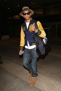 Pharrell Williams gives a thumbs up for his flight at LAX **USA ONLY**