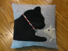 Whimsical and sweet pillow featuring a sleeping black kitty cat and a curious little white mouse peeking at him. This pair looks very realistic. Ive used plush material to make them soft and furry. The mouses one ear sticks off the pillow, he has a black bead eye and grey whiskers. The background of the pillow is a grey wool felt. I make this pillow year round but I thought it would be fun to add a festive touch this time by adding candy cane collars and silver bells. This pillow is my own…