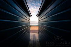 An interesting view between beach huts look through the the sea on a lovely sunny day during the end of the afternoon