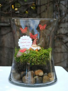 """Love Garden 0 How to make it: Place rocks on bottom of glass container. Put a little soil on top and some green grass ground covering on top of that. Make butterflies with paper punch and red glittered paper, using clear glue to affix them to the glass. Print """"There is GNOME one like you"""" on cardstock and punch out."""