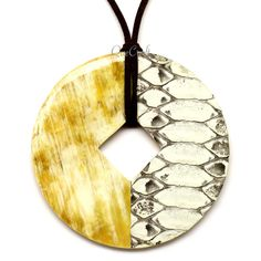 A beautiful pendant handmade from buffalo horn and python leather. High polish finish. Lightweight. Actual colors may vary. 3.15 (8cm) diameter.