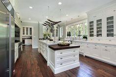 Luxury white kitchen with island and hardwood flooring